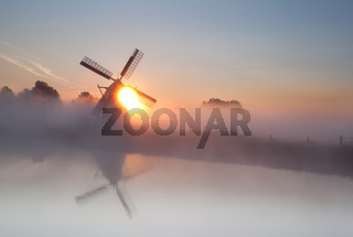sun behind windmill and fog