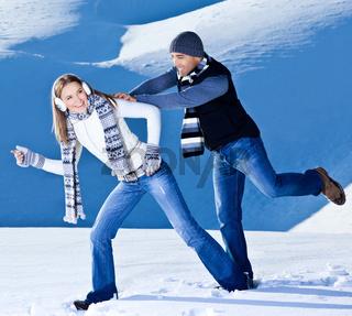 Happy couple having fun in snow
