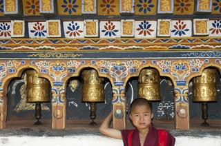 Kindermönch vor Gebetsmühlen, Bhutan