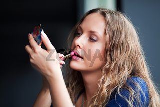 Beautiful woman applying a lipstick