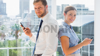 Smiling business team standing back to back and texting