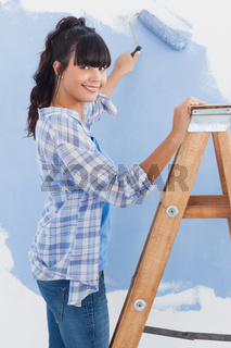 Woman using paint roller smiling at camera