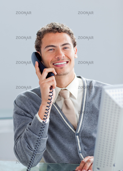 Smiling businessman on phone at his desk