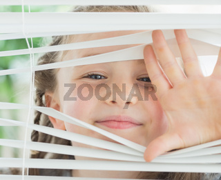 Smiling girl looking through the blinds