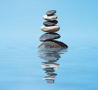 Zen balanced stones stack in lake  balance peace silence concept