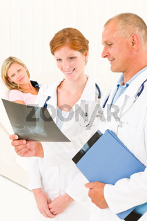 Medical doctors look x-ray patient broken arm