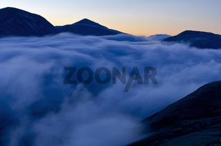 Blick ueber das nebelverhuellte Tal Atndalen zu Gipfeln im Rondane Nationalpark, in der Ferne der Gipfel Snoehetta, Hedmark