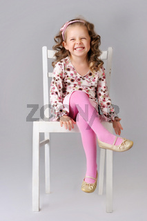 Cute little child sitting on the chair and smiling