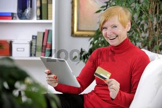 Seniorin mit Tablet-PC und Kreditkarte