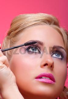 Beautiful woman applying mascara on her eyelashes