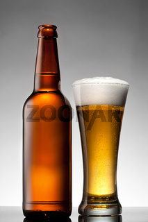 Beer in glass and bottle on white
