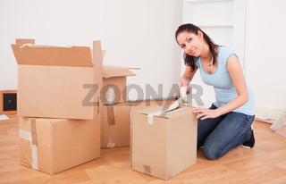young brunette taping a box