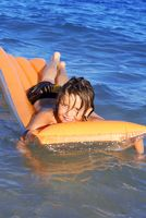 young kid floating in sea playing on airbed or lilo