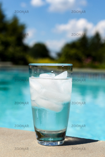 Glass of water with ice cubes on side of pool