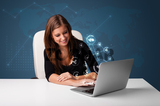 Young lady sitting at desk and typing on laptop with social network icons