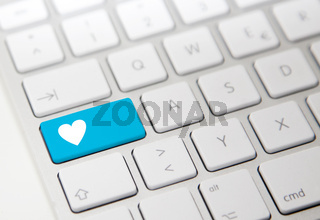 White computer keyboard with blue 'heart' button