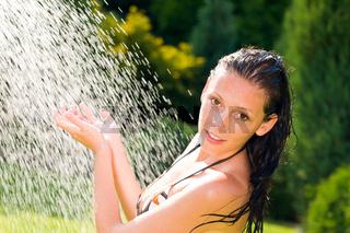 Summer garden smiling woman swimsuit splash water