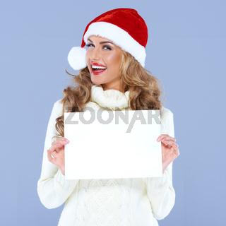 Happy woman in Santa hat holding blank board