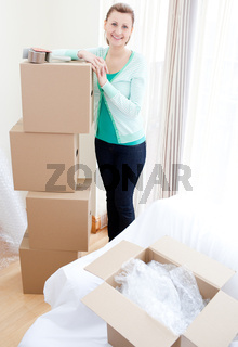 Smiling woman closing various boxes
