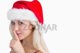 Woman in santa hat making silence gesture