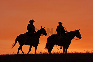 Silhouettes of cowboys on horseback at sunset