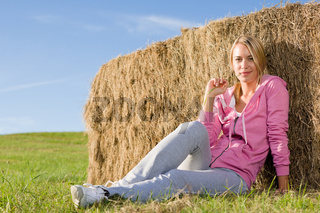 Sportive young woman relax by bales sunset