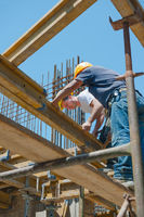 Construction workers placing formwork beams