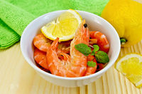 Shrimp in a white bowl with lemon slices