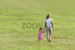 Mother with daughter go on grass in clean floor