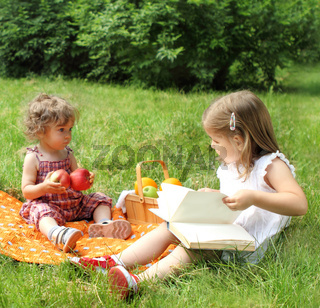 Children reading the book on picnic