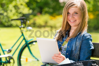 Adolescent girl using tablet computer in park