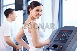 An attractive young woman on a treadmill