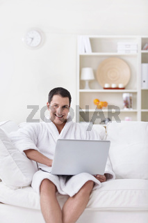 A young man in a white robe with laptop