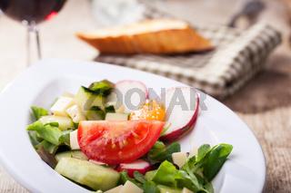Salat mit Käsewürfeln und Wein
