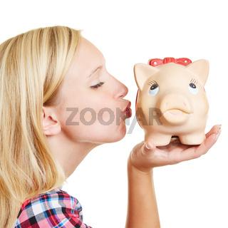 Blonde Frau küsst Sparschwein