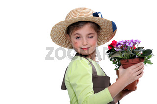 Little girl wearing straw hat holding plant pot