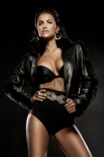Alluring woman in black clothes posing over dark background