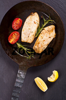 fish fillet fried with fresh herbs in a pan