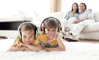 Adorable siblings listening music with headphones