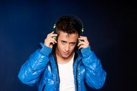 Young man listening music with headphones portrait on blue background