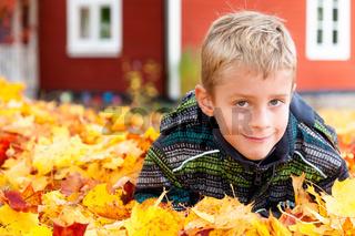 Kleiner blonder Junge spielt im Herbstlaub