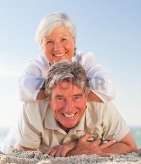 Senior couple lying down on the beach