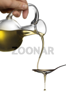 Pouring oil from jar on spoon isolated on white