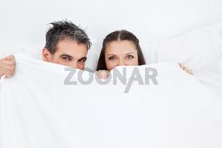 Mann und Frau verstecken sich hinter Bettdecke