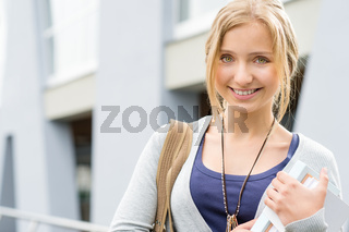 Young happy woman holding books to school