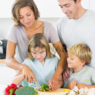 Mother teaching daughter to slice vegetables as father and son are watching