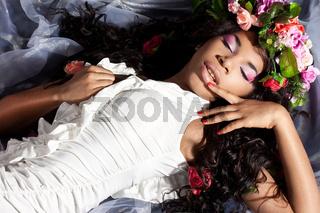 Elegant mulatto girl with circlet of flowers