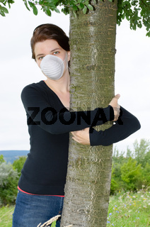 Young environmentalist in face mask hugging a tree