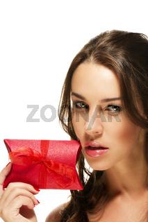 schöne frau hält rotes geschenk an ihr gesicht
