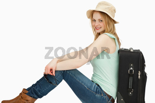 Joyful woman sitting near a suitcase